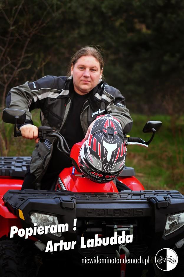 Mężczyzna ubrany w kombinezon motocyklowy. Siedzi na czerwonym kładzie. Opiera się lewą ręką o kierownicę, prawą trzyma na manetce przyśpieszenia. Na przednim reflektorze wisi  czarno czerwono biały kask. W tle teren zielony.