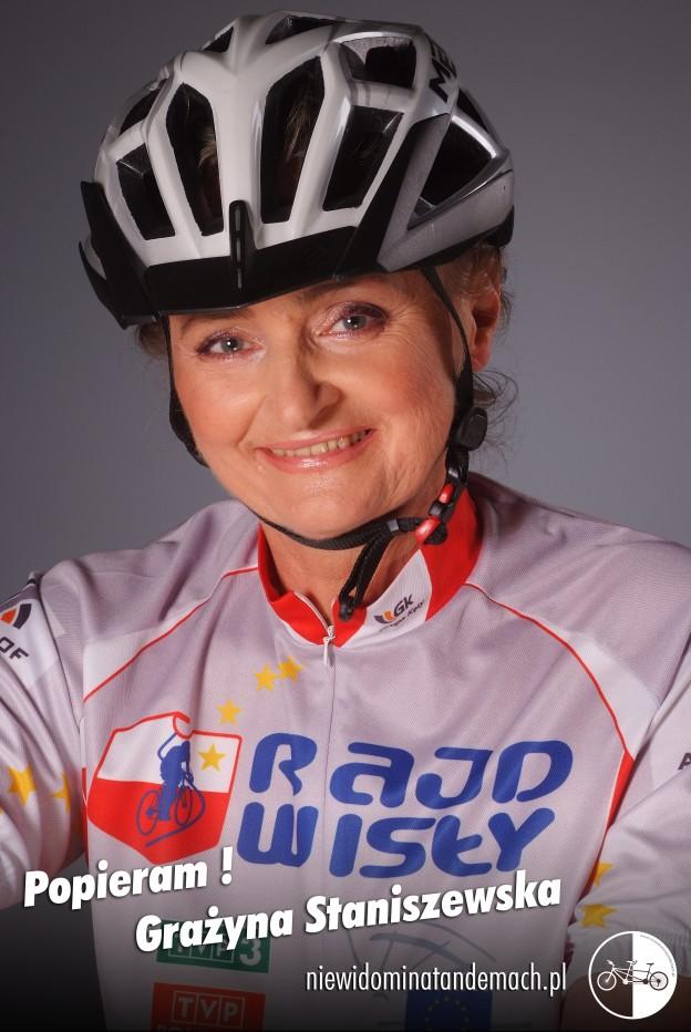 Na szarym tle, popiersie uśmiechniętej kobiety ubranej w jasny strój kolarski. Na głowie szary kask kolarski, na bluzie granatowy napis Rajd Wisły i biało czerwony zarys graficzny Polski, w nim sylwetka rowerzysty na linii symbolizującej rzekę Wisłę.