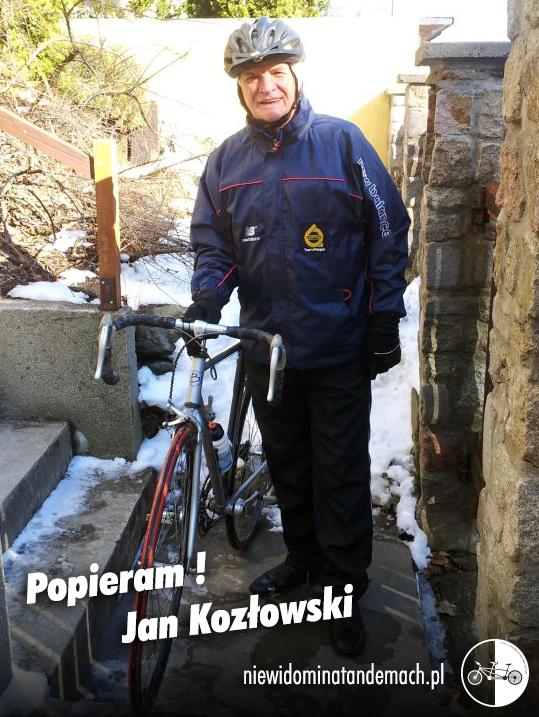 W środku kadru postać stojącego mężczyzny trzymającego prawą ręką kierownicę roweru szosowego. Sceneria zimowa. Po lewej stronie kadru dwa stopnie betonowych schodów. Po prawej stronie kadru kamienne filary ogrodzenia. Uśmiechnięty mężczyzna ubrany w granatową kurtkę i spodnie, na głowie czarny kask rowerowy. W tle skarpa porośnięta krzakami i śnieg.