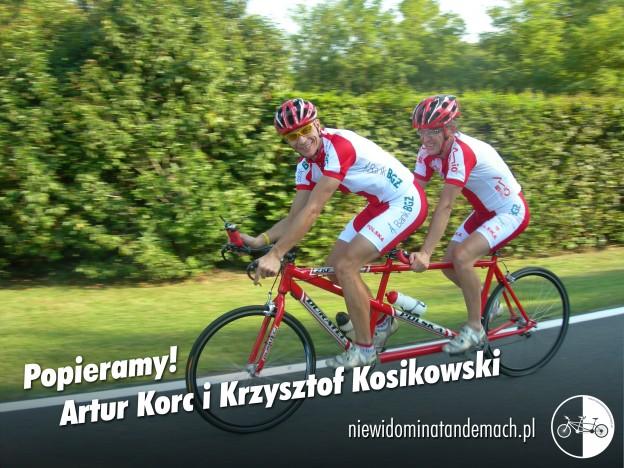 Szybka jazda, dwaj mężczyźni ubrani w biało czerwone letnie stroje kolarskie na czerwonym tandemie szosowym. Dłonie bez rękawiczek ułożone na uchwytach kierownic. Na głowach czerwono czarno białe kaski rowerowe. Prowadzący tandem z uśmiechem spogląda przez lewe ramię w kierunku obiektywu. Równy szary asfalt. W tle rozmyta ściana zielonego żywopłotu.