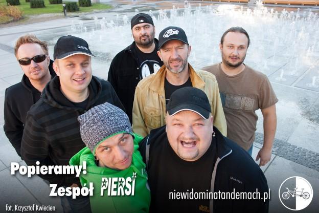 Grupa muzyczna na tle miejskiej fontanny, z której tryska w górę  kilkadziesiąt strumieni wody. Siedmiu uśmiechniętych, stojących w grupie, ramię w ramię mężczyzn wpatrzonych w obiektyw aparatu fotograficznego.